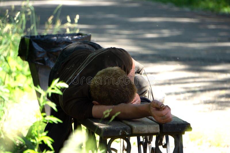 Dronken mensenslaap in park op houten bank stock afbeelding
