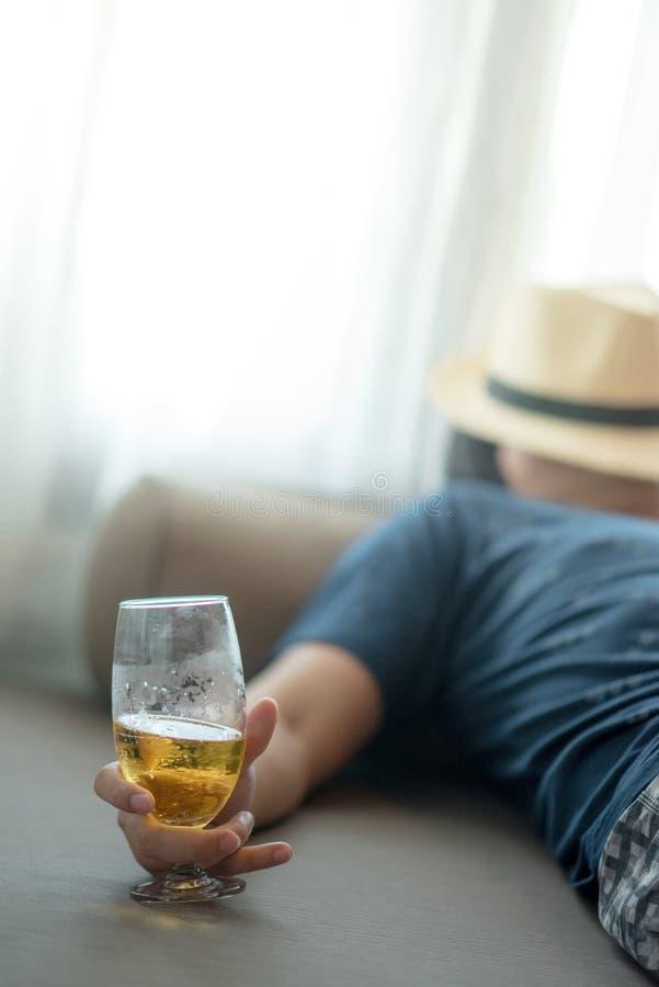 Dronken mensenslaap terwijl het houden van een glas bier stock foto