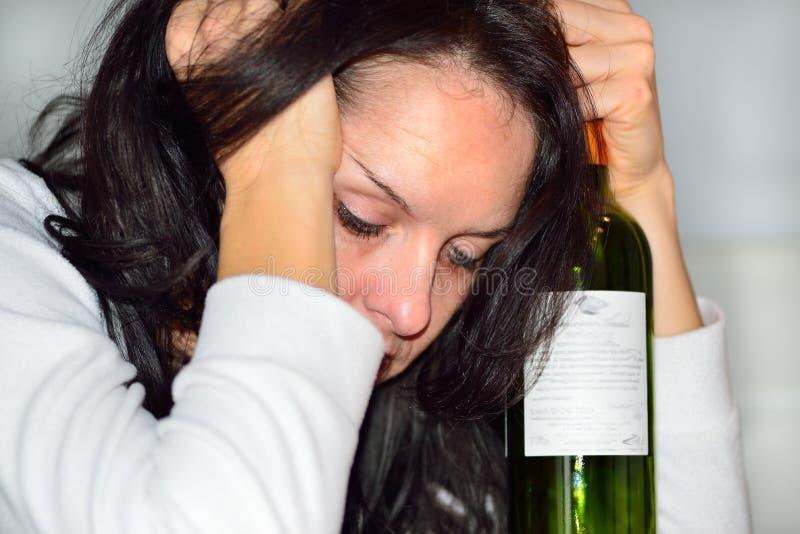 Dronken vrouw met rode wijnfles royalty-vrije stock afbeeldingen