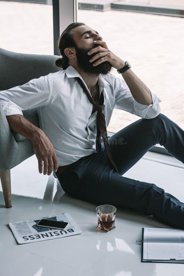 Dronken zakenmanzitting op vloer stock foto