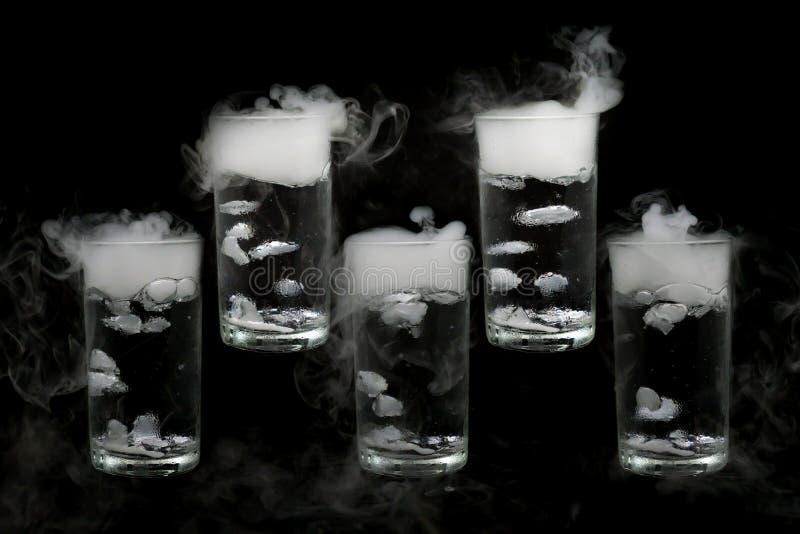 Droog die ijs vijf in een glas water op zwarte achtergrond wordt geïsoleerd de rook, sluit omhoog royalty-vrije stock foto