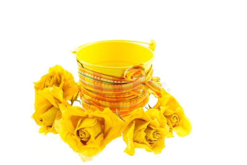 Droog gele rozen en emmer met oranje lint stock afbeeldingen