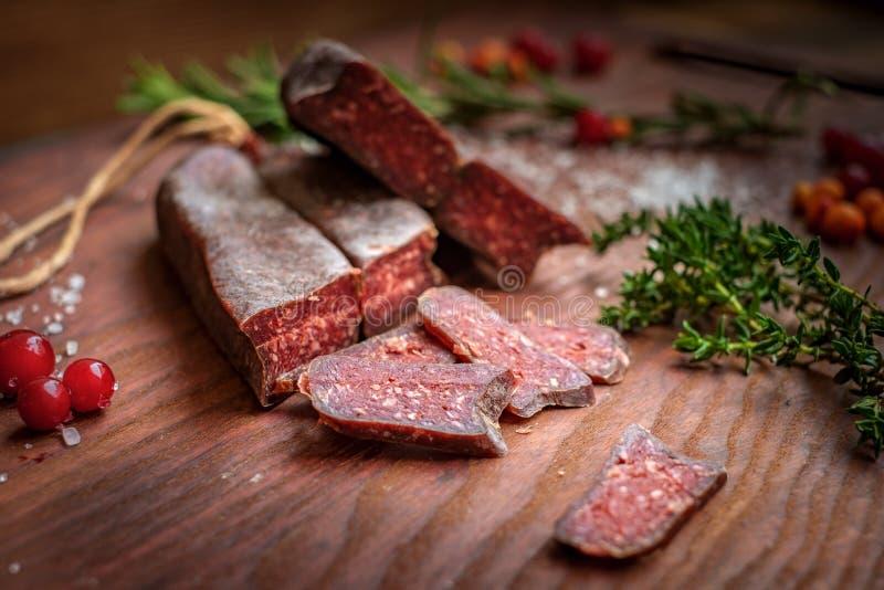 Droog-genezen die salami op houten achtergrond met druiven en kruiden wordt gesneden royalty-vrije stock fotografie