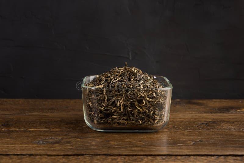 Droog groene thee in de transparante die kom op houten lijst aangaande zwarte wordt geïsoleerd royalty-vrije stock afbeeldingen