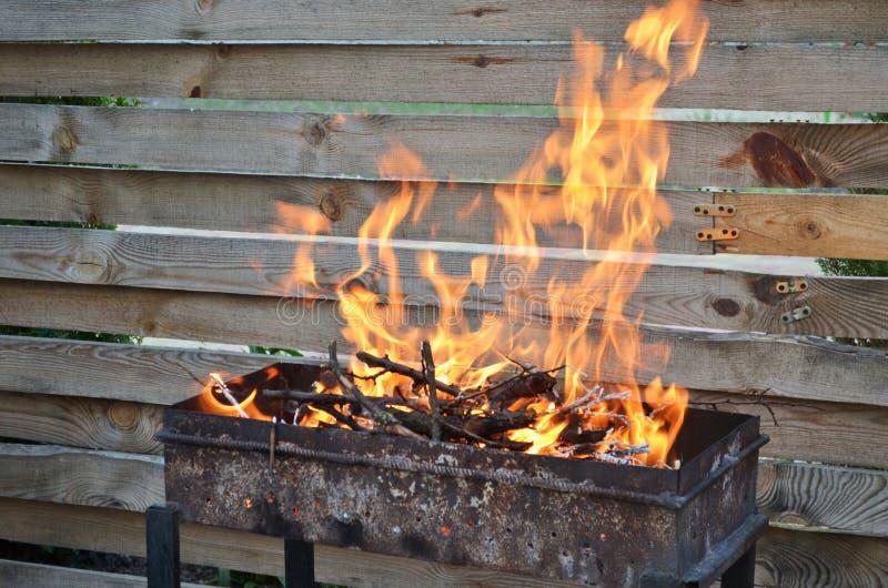 Droog hout voor het roosteren van brandwond met een grote vlam op de grill, op een achtergrond van een houten omheining royalty-vrije stock afbeeldingen