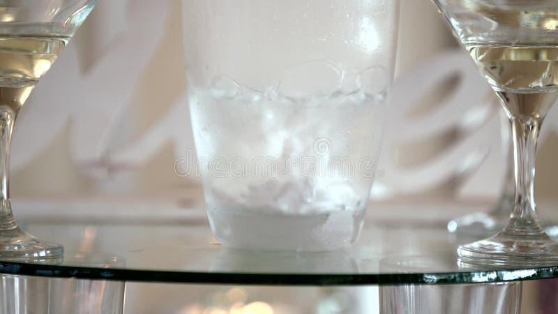 Droog ijs De mensen` s hand giet een alcoholische drank Voor de lijst, heel wat schotels waarin een drank giet Langzame Motie stock afbeelding