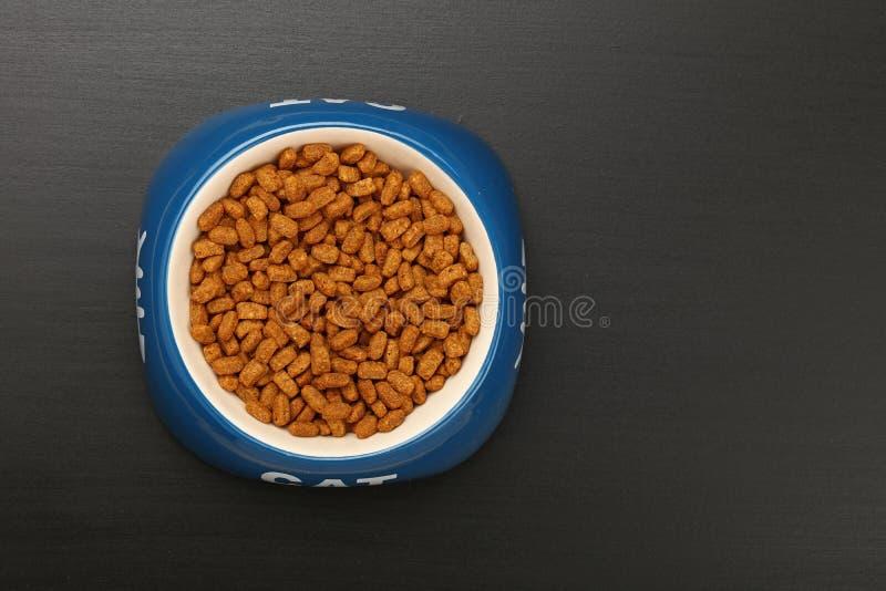 Droog kattenvoedsel in ceramische kom op zwarte vloer stock fotografie