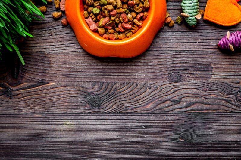 Droog kattenvoedsel in kom op houten hoogste mening als achtergrond stock afbeelding