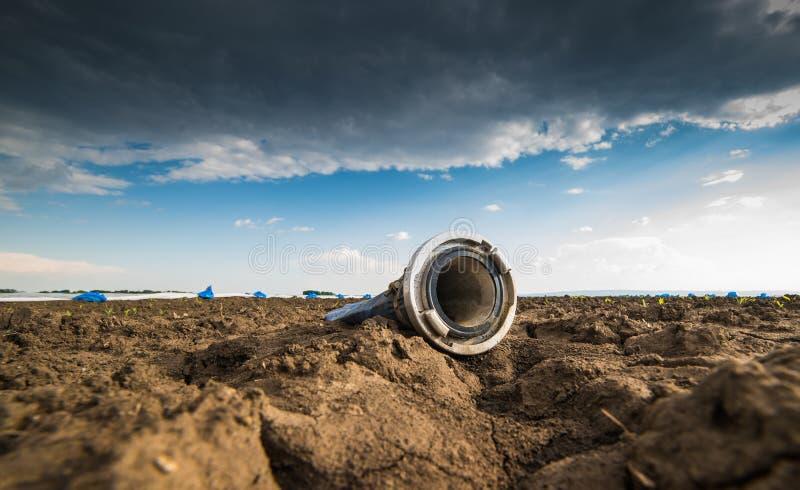 Droog land - droogte - en slang voor het water geven stock fotografie