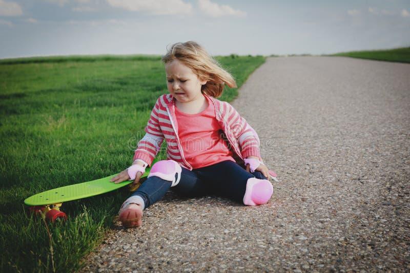 Droog meisje van skateboard, verwonding stock afbeeldingen