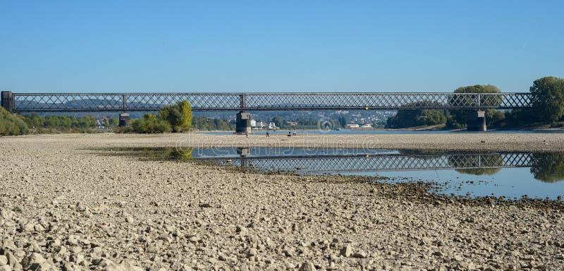 Droog rivierbed met stenen, zichtbare oude spoorwegbrug stock afbeeldingen