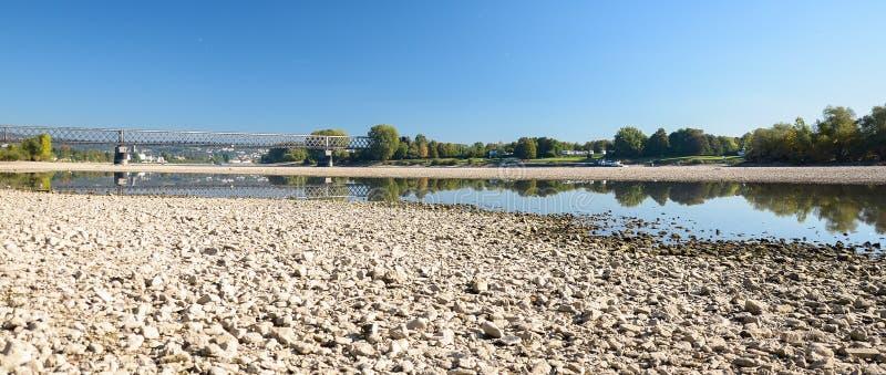 Droog rivierbed met stenen, zichtbare oude spoorwegbrug royalty-vrije stock fotografie