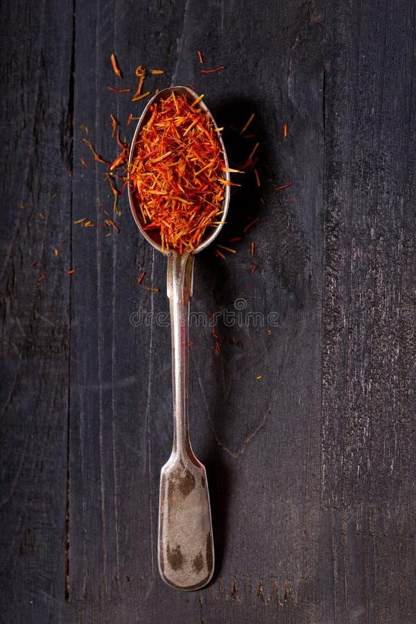 Droog saffraankruid in een lepel op houten lijst stock afbeelding
