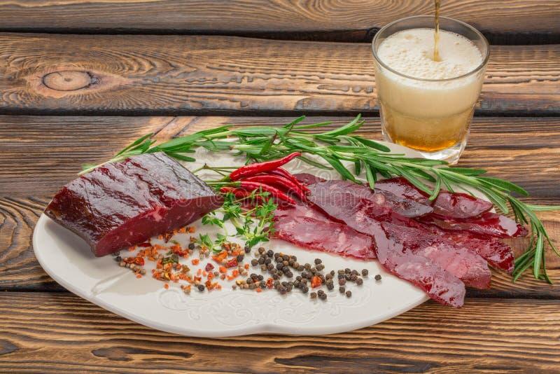 Droog vlees met verse kruiden, Spaanse pepers, specerijen op een plaat het bier wordt gegoten in een glas over houten achtergrond stock afbeeldingen