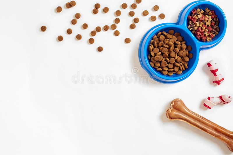 Droog voedsel voor huisdieren in kom en been op witte hoogste mening als achtergrond royalty-vrije stock afbeeldingen