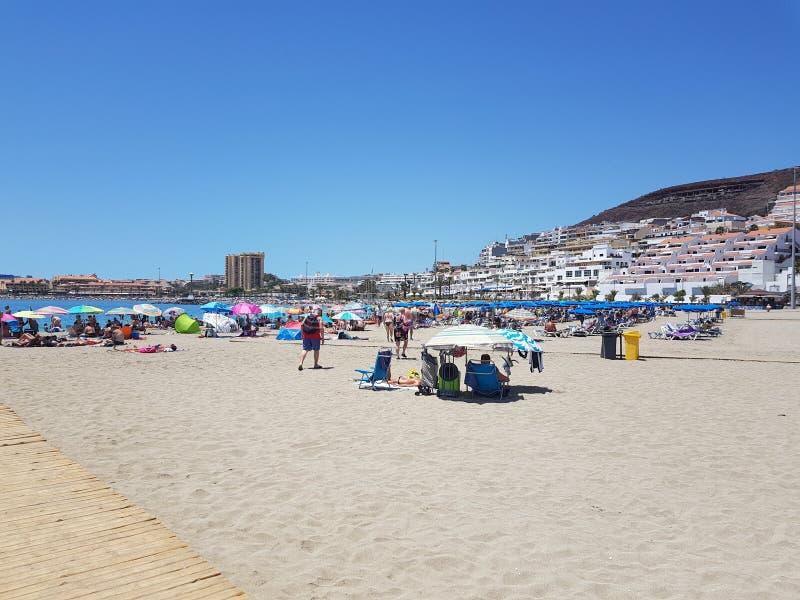 Droog zandige strandmening van de zon die van vakantiemakers en in schaduw onder parasols baden zitten stock foto's
