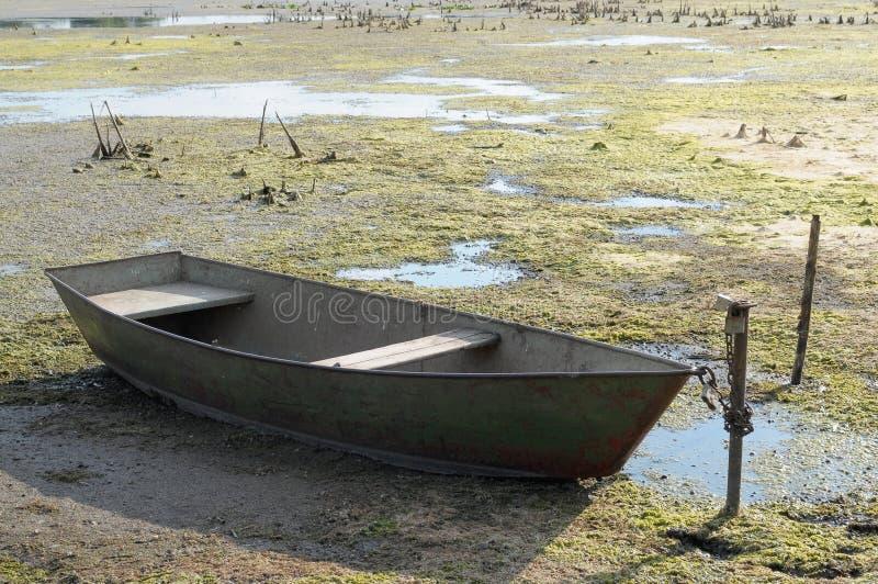 Droogte in de hete zomer Droge rivier zonder water en boot stock foto's