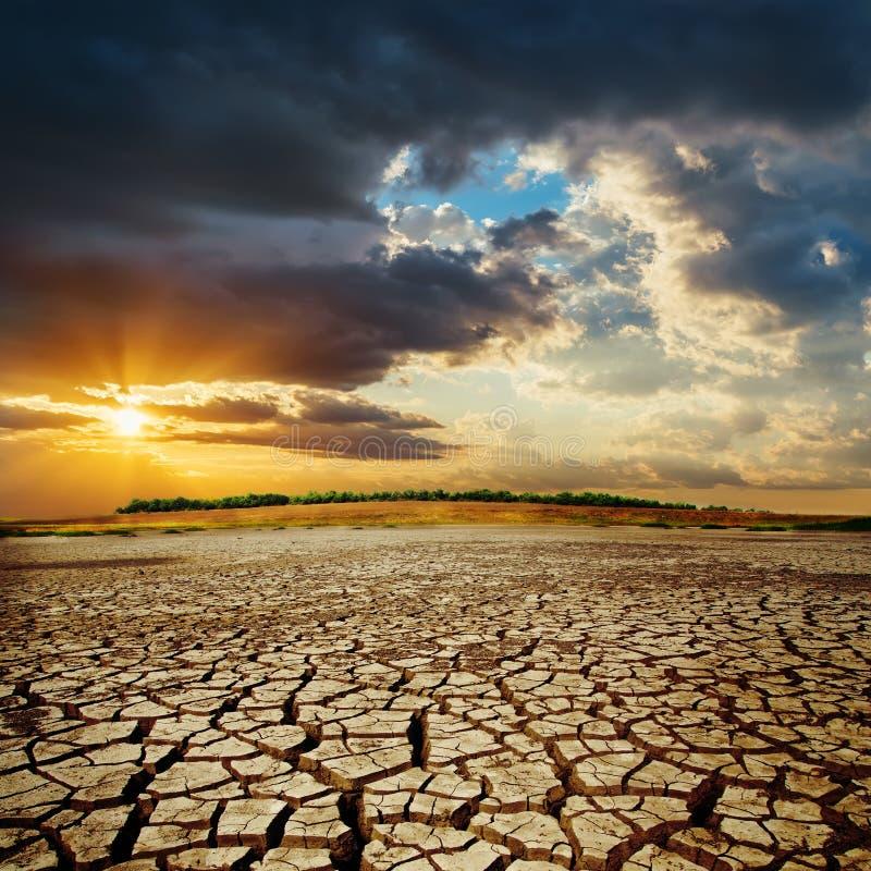 Droogteaarde in zonsondergang Dramatische hemel over woestijn stock foto's