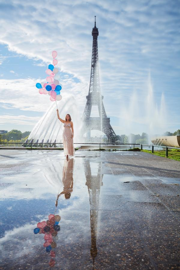 Droomreis - jonge vrouw die met ballons dichtbij de Toren van Eiffel in Parijs loopt stock foto's