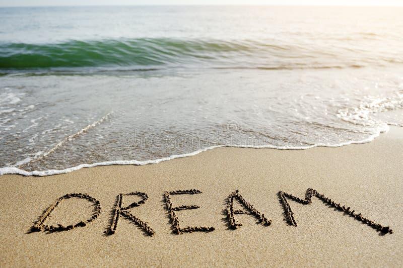 Droomwoord op strandzand wordt geschreven - positief het denken concept dat royalty-vrije stock afbeeldingen