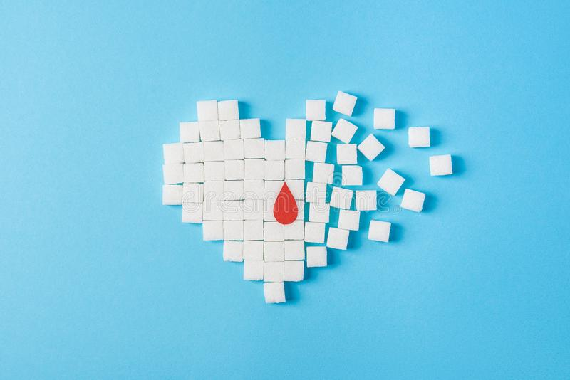 A drop of blood on broken heart made of pure white cubes of sugar isolated on blue background, World diabetes day royalty free stock photography