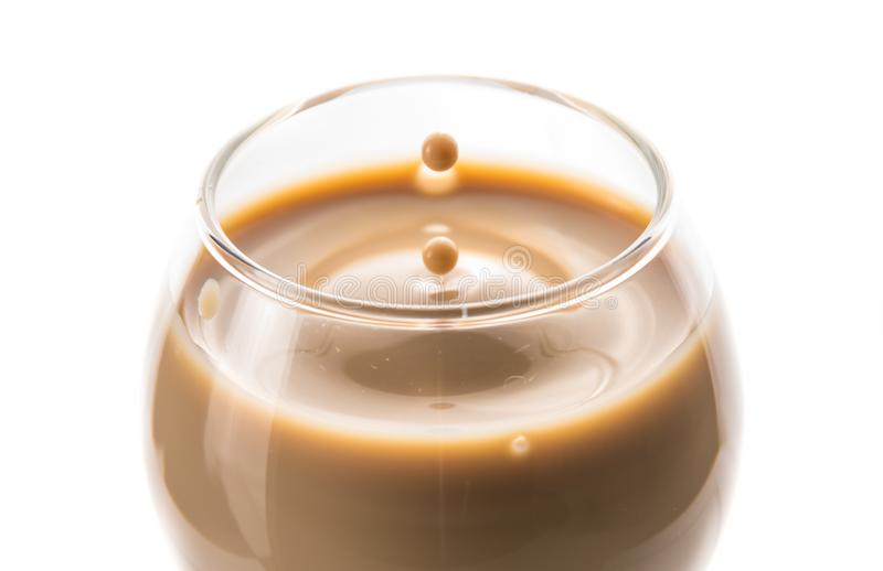 A drop of chocolate liquor dropped into a round glass left waves and a splash royalty free stock photography
