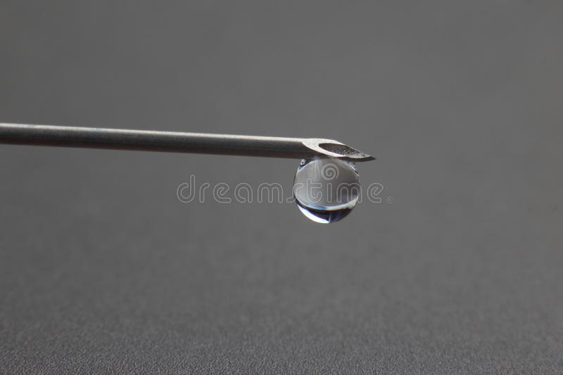 Drop of liquid hangs on the tip of a medical injection needle. The drop of liquid hangs on the tip of a medical injection needle stock photography