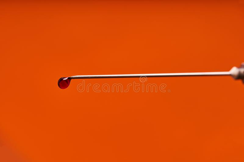 A drop of medicine on the tip of a medical injection needle. Red background.  stock photography