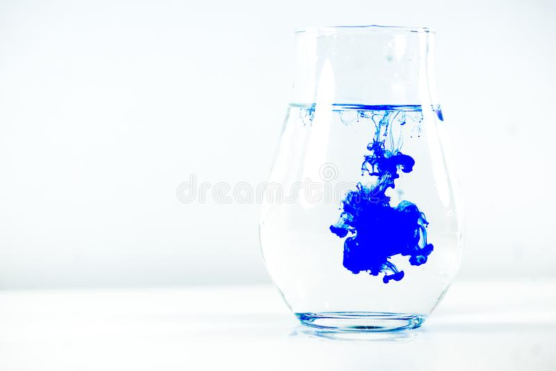 A drop of paint in a jar of water royalty free stock photography