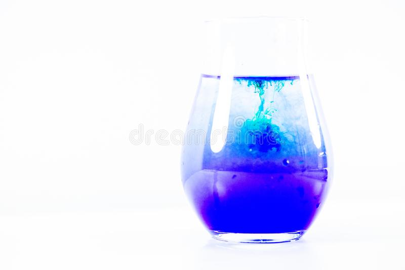 A drop of paint in a jar of water stock image