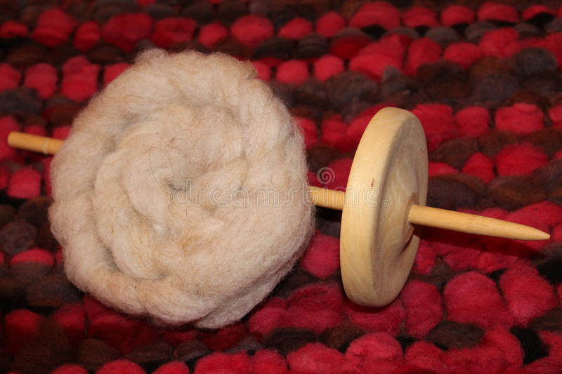 Drop spindle. With sheep wool roving stock images