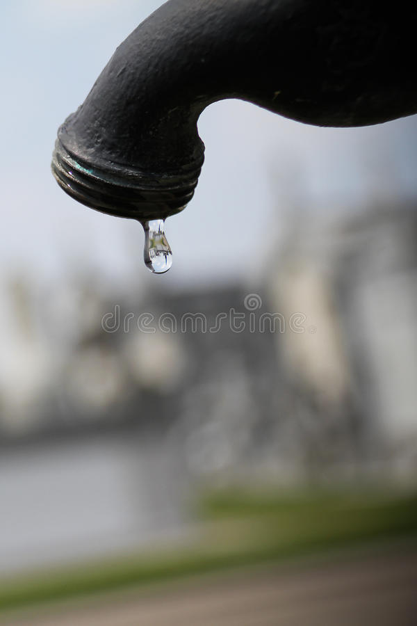 Drop of Water. A drop of water from a spout in a cemetery. Shot in New Orleans. Clouds and religious grave markers visible in drop stock photo