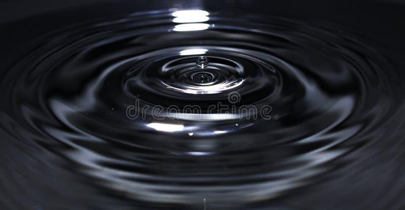 Drop of water bouncing stock image