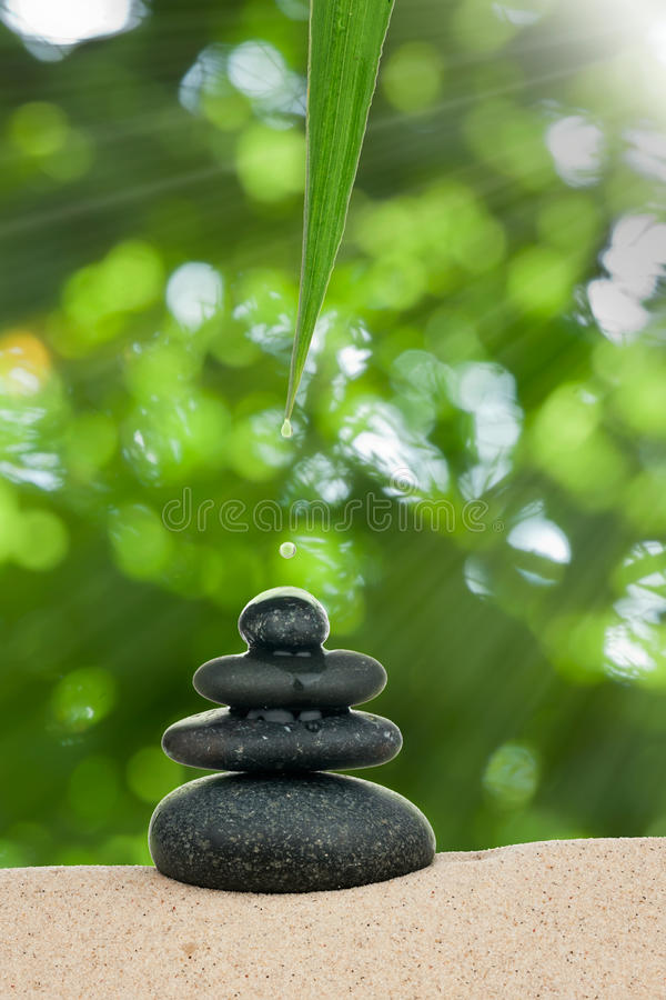 A drop of water drips on the pyramid stone stock photos