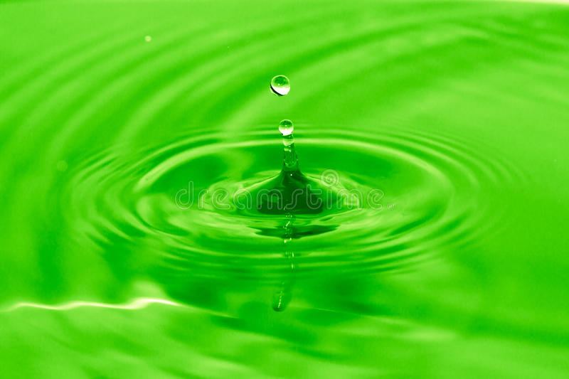 A drop of water falls into the green water stock photo