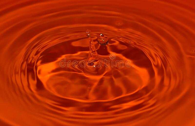 Drop of water hitting orange bowl royalty free stock photo