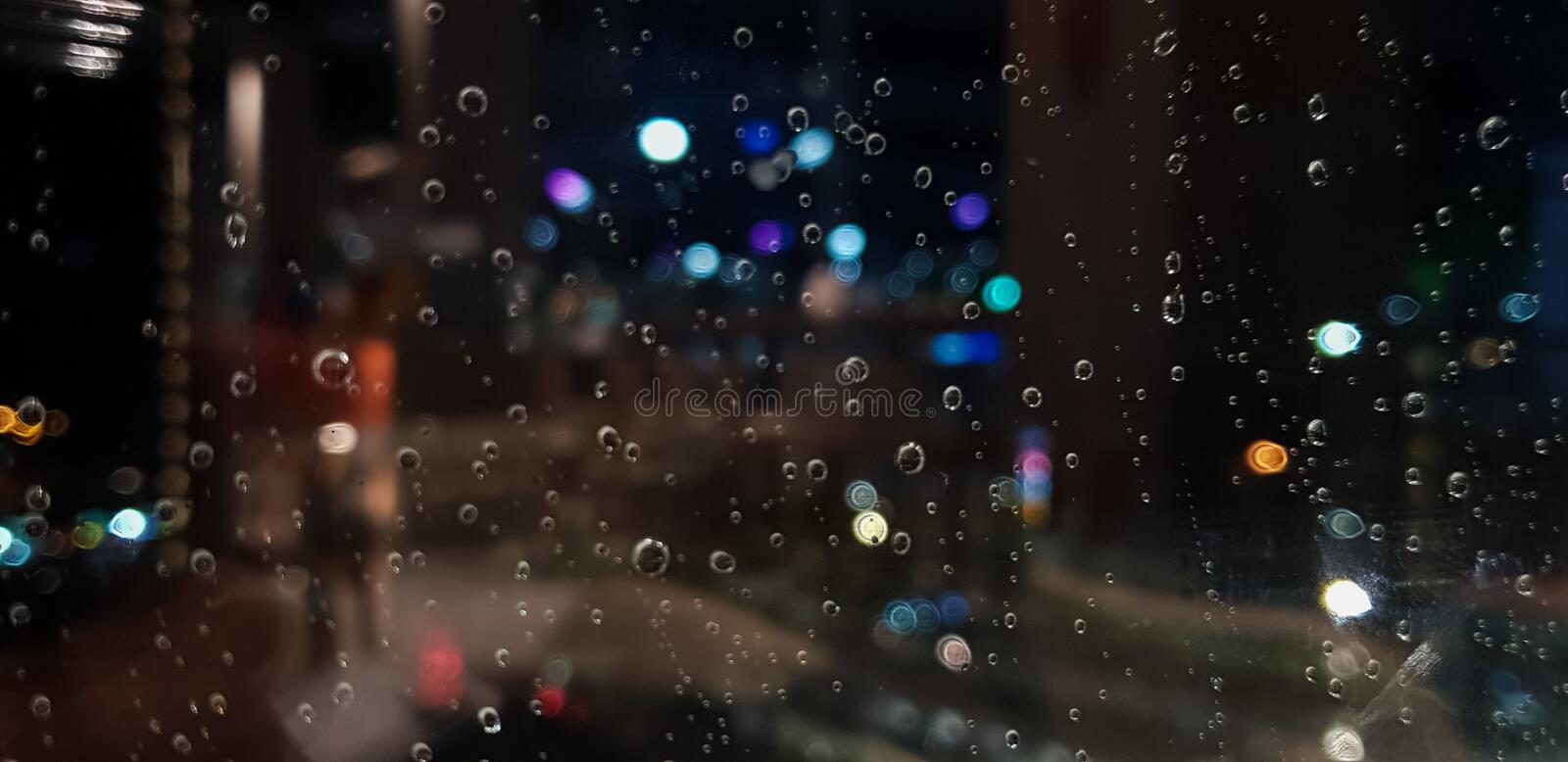 Drop of water rain on window glass surface with City light blur background. Photos from mobile.  royalty free stock images