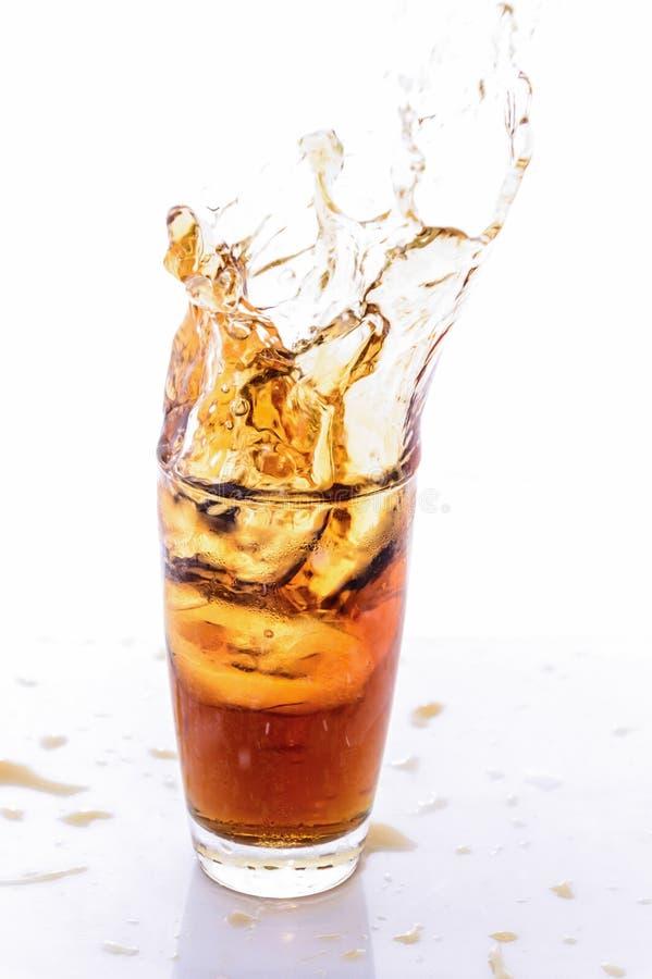 droped glass is för cola kub royaltyfria bilder