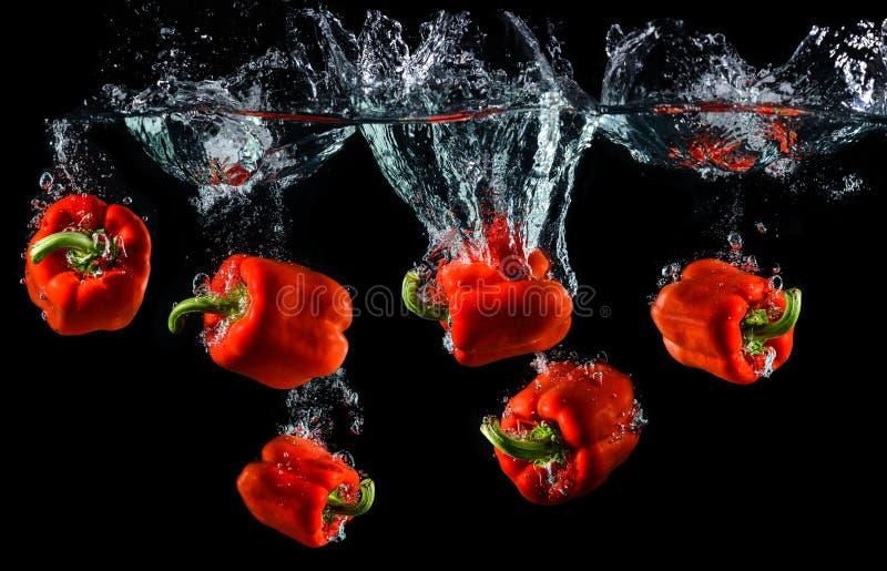 droping红色甜椒或辣椒粉的水 免版税图库摄影