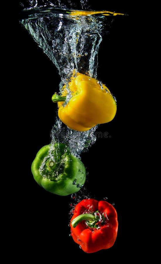Droping πιπέρι ή πάπρικα κουδουνιών νερού στοκ εικόνες