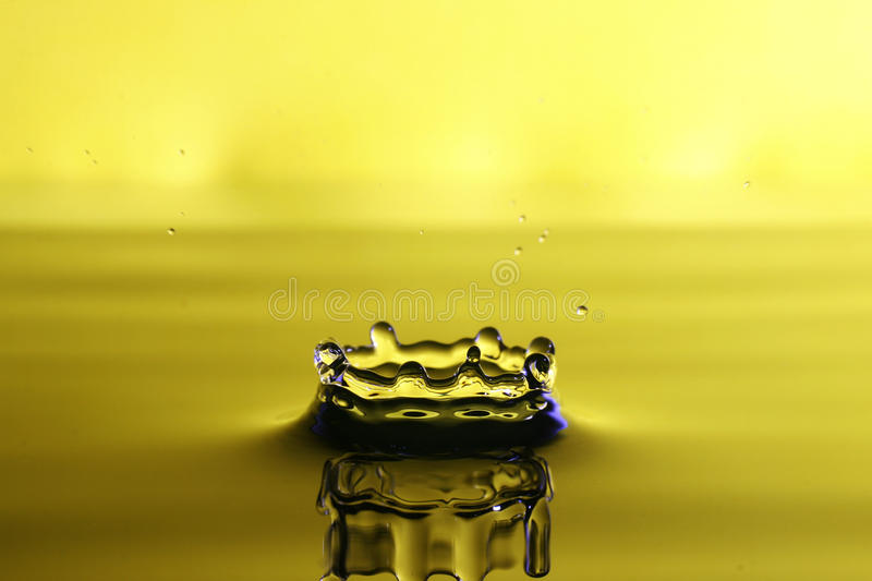 Droplet of water from a splash. With yellow background stock photography