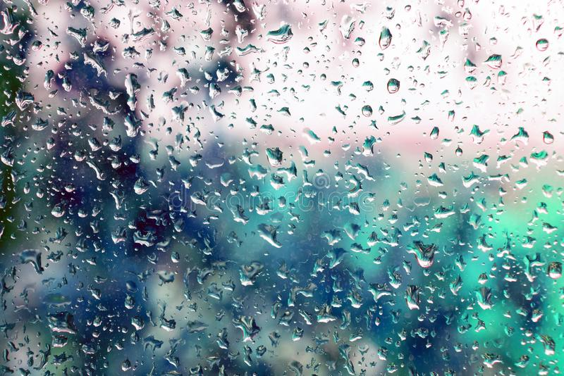 Droplets of rain on a window. Glass on a blurred background and trees with green foliage