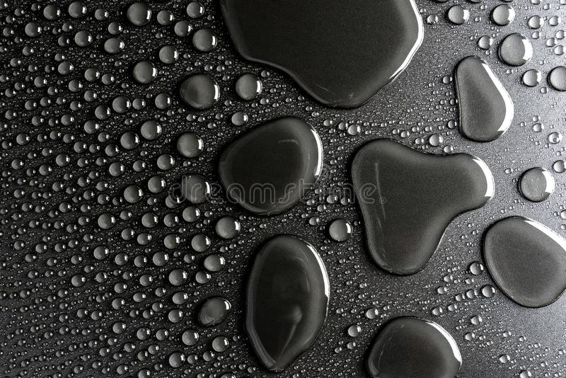 Droplets of water on a black, matte background illuminated with a delicate light. Droplets of water on a black, matte background illuminated with a delicate stock photography