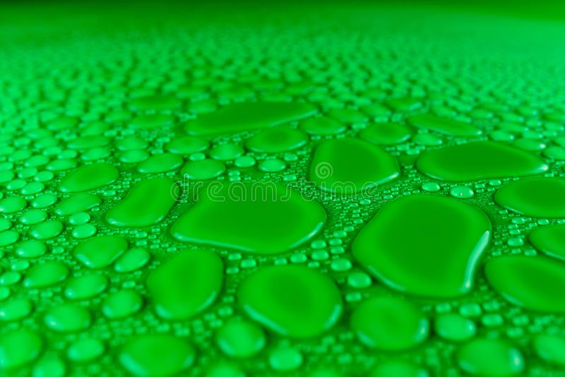 Droplets of water on a green, matte background illuminated with a delicate light. Droplets of water on a green, matte background illuminated with a delicate stock photos