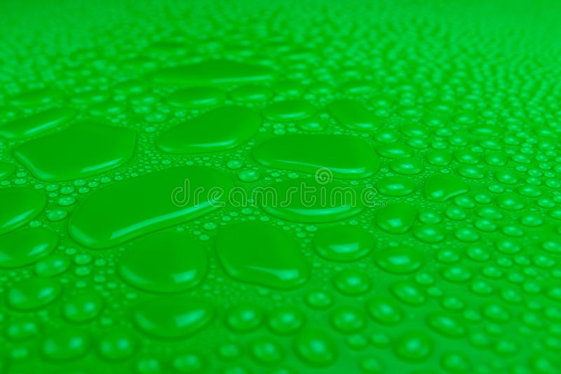 Droplets of water on a green, matte background illuminated with a delicate light. Droplets of water on a green, matte background illuminated with a delicate stock photo