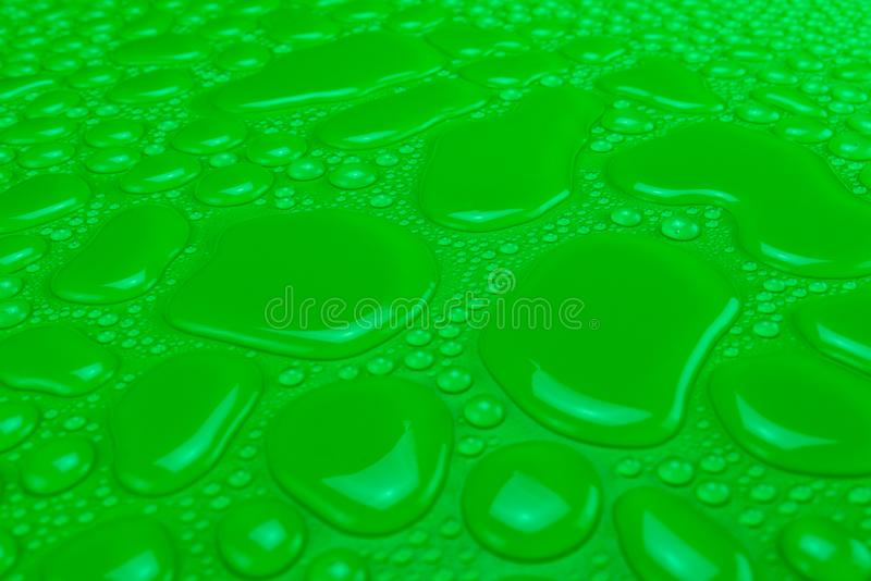 Droplets of water on a green, matte background illuminated with a delicate light. Droplets of water on a green, matte background illuminated with a delicate royalty free stock image