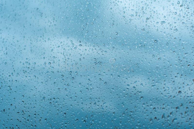 Droppar av regn på fönsterexponeringsglaset blir grund DOF Fönster efter regn Bakgrund för blått vatten med vattendroppar arkivbilder