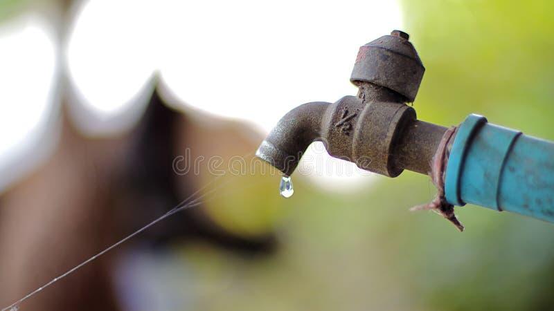 Droppar av vatten från den gamla vattenkranen royaltyfri foto