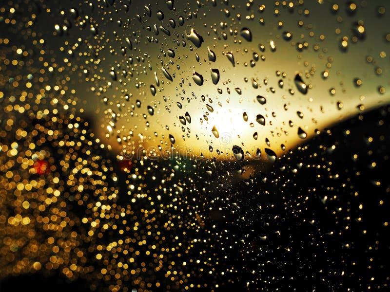 Droppar av vatten på bilexponeringsglaset som kör på vägen i regnet arkivfoton