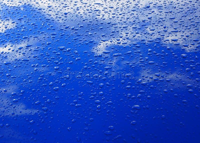 Droppar av vatten på den blåa bilen sätter på en hätta royaltyfria bilder